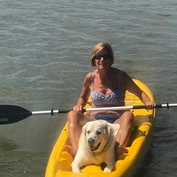 Woman in kayak with golden retriever dog