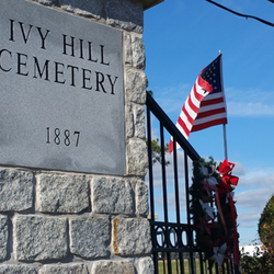 SIgn at the entrance to Ivy Hill Cemetery with American Flag