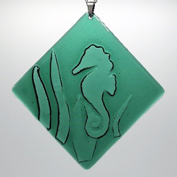 Example of fused glass ornament with seahorse on green background