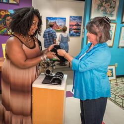 An artist showing her work to a customer at the Arts Center