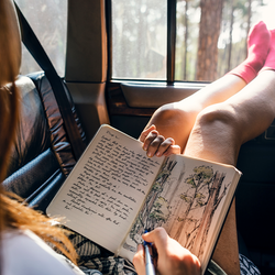 Girl writing and drawing in journal while riding in car