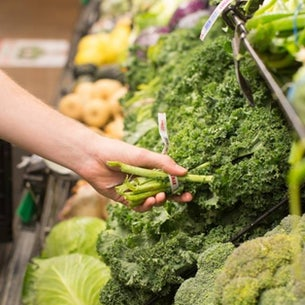 Produce section of grocery store womans hand reaching out to pick brocolli