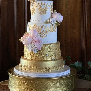 Beautiful tiered wedding cake in gold and white with decorative flowers