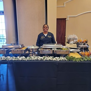 Crystal standing behind table of food by Crystals Catering and Sweet Treats